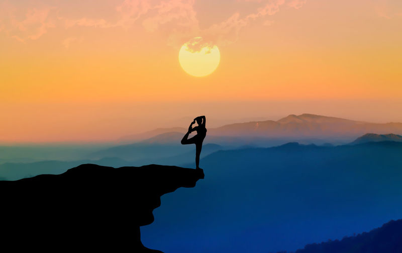 Silhouette person on cliff against sky during sunset