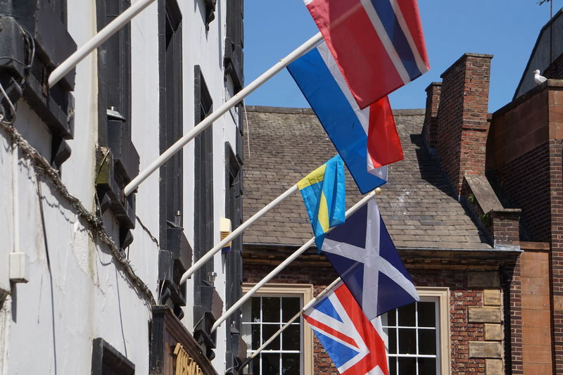 Low angle view of flags hanging against buildings