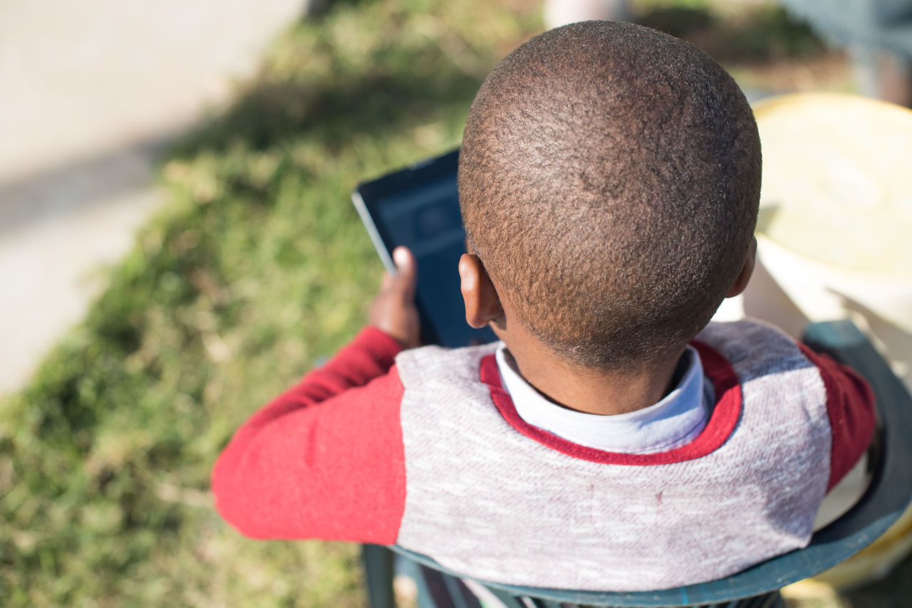 Rear View Of Boy Using Digital Tablet While Sitting On Chair