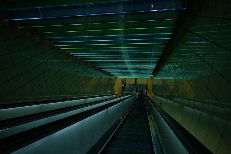 Escalator in illuminated underground walkway