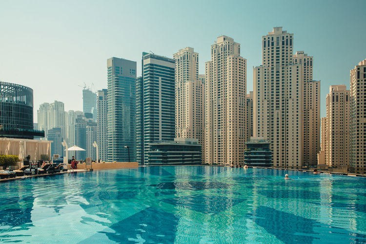 Modern buildings by swimming pool in city
