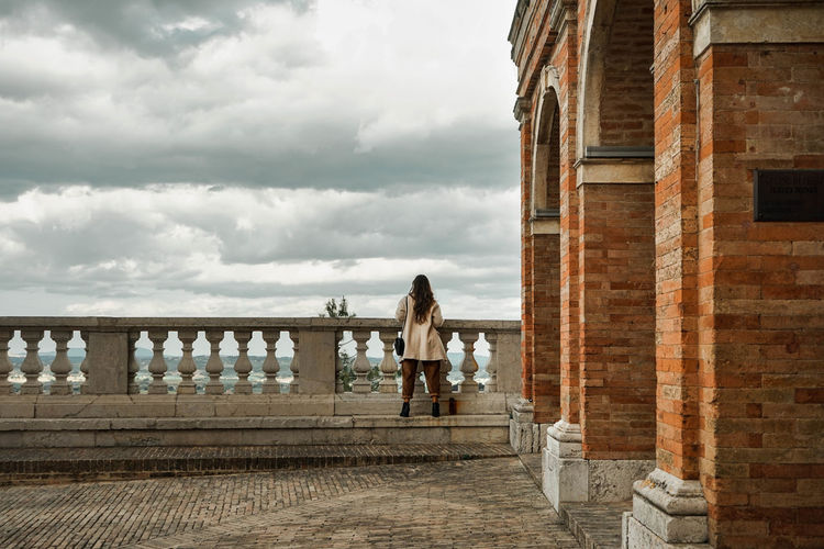 Rear view of women standing on railing against cloudy sky in treia