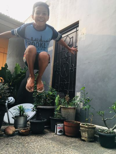 jumping at home INDONESIA Happiness Playful Jumping Brother One Person Potted Plant Plant Real People Lifestyles Front View Leisure Activity Young Men Growth Young Adult Outdoors Day