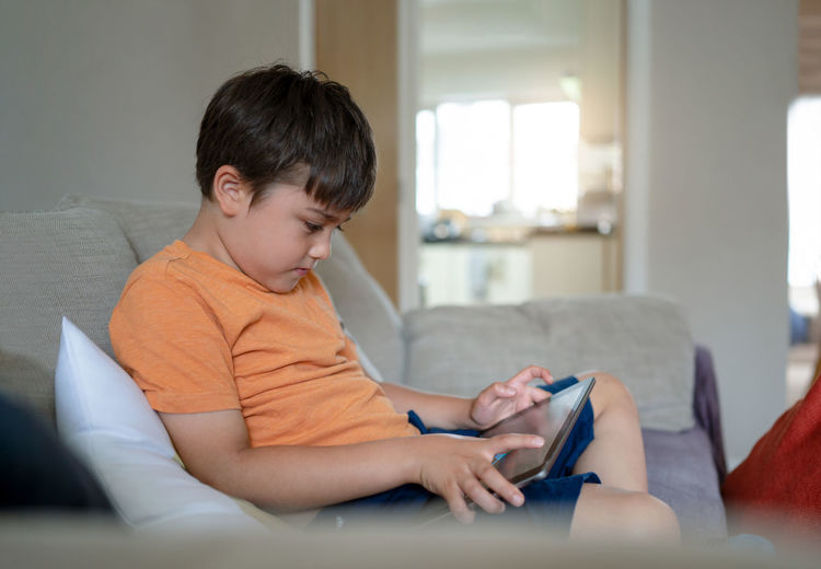Boy sitting on mobile phone at home