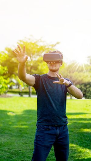 Man Gesturing While Using Virtual Reality Simulator On Grassy Field At Park
