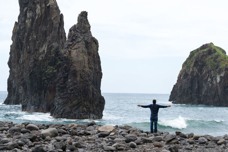 Man with arms wide open looking at Ribeira da Janela islet in Madeira Madeira Portugal Island Ilha Landscape Nature Islet Ribeira Da Janela Seascape Panorama Panoramic Rock Outdoors Sea Ocean Atlantic Man Travel Destinations Traveler Arms Raised Best  Waves Ilheu Porto Moniz Portuguese