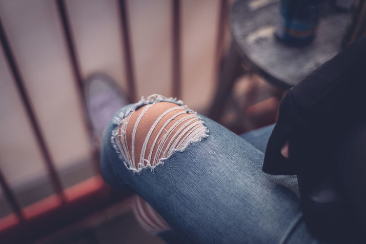 Casual Clothing Close-up Lifestyles Person Relaxation Ripped Jeans Selective Focus Sitting Woman