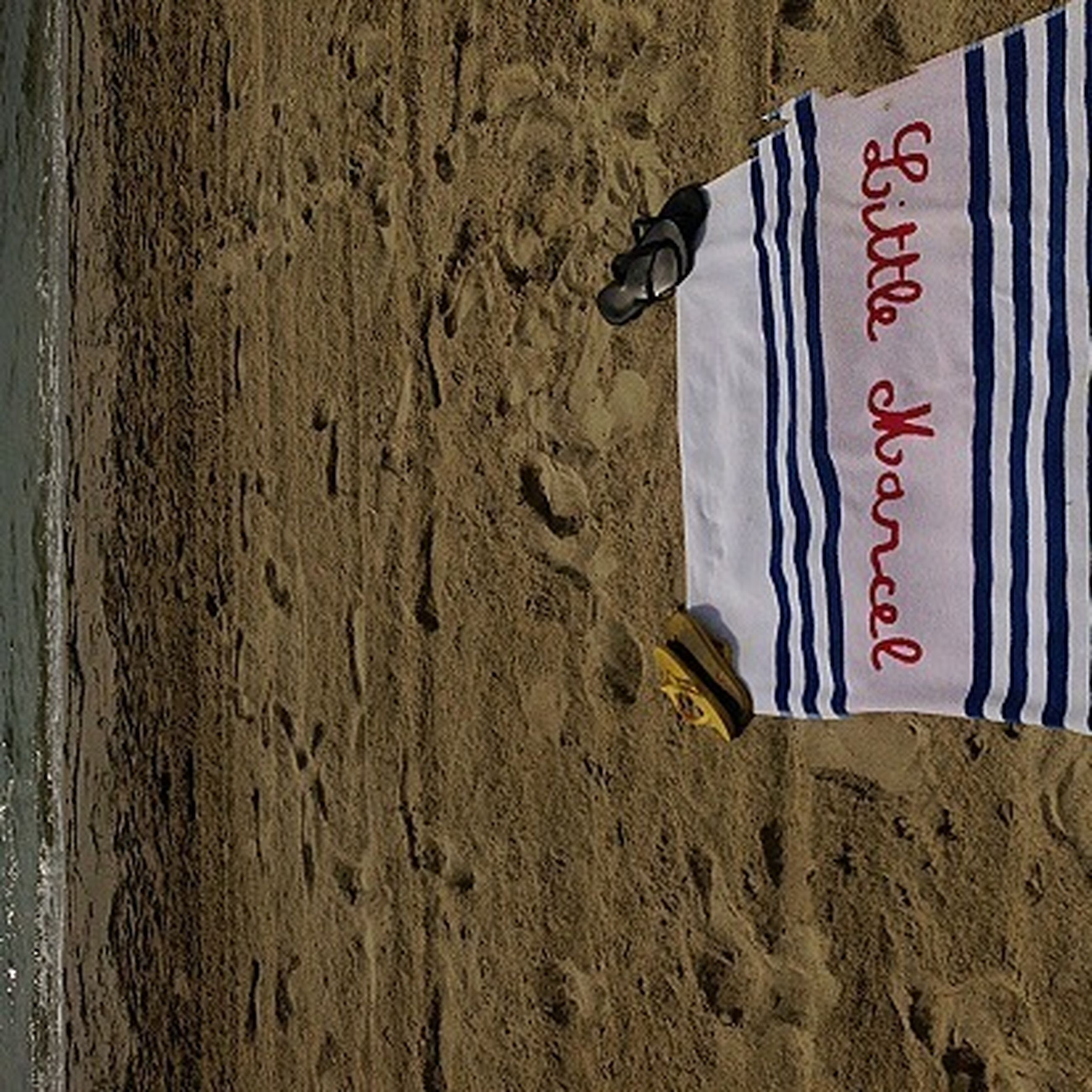 text, beach, sand, western script, communication, shore, sea, wave, day, water, outdoors, sunlight, guidance, surf, capital letter, footprint, sign, no people, close-up, wall - building feature
