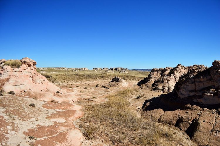 Different size formations Sunshine Outdoors In The Distance. West Of Lusk Wyoming Shadows Pasture Rock Formations Country Side Rural Scene Clear Sky Blue Rock - Object Landscape