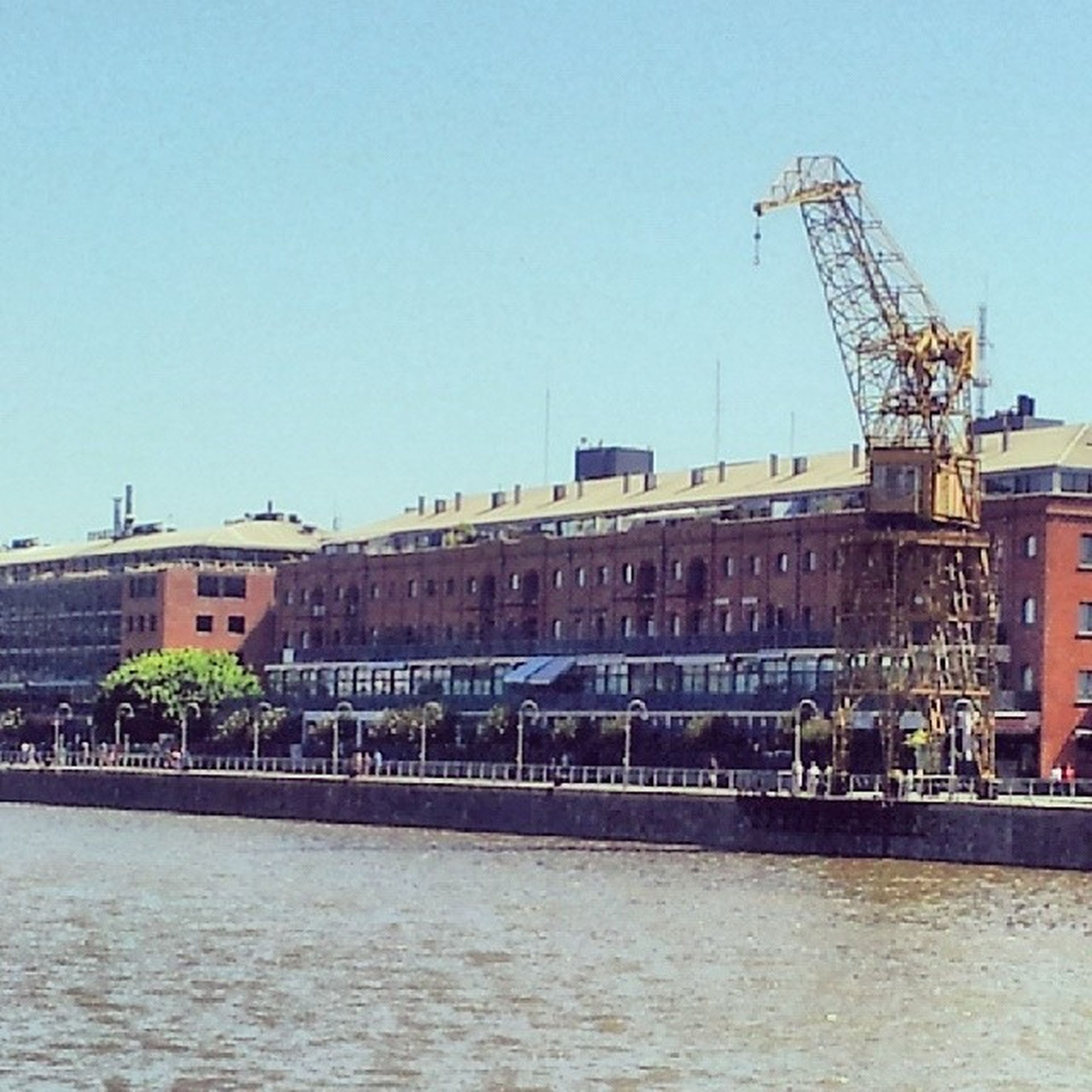 architecture, building exterior, built structure, clear sky, crane - construction machinery, waterfront, city, copy space, residential building, water, residential structure, development, crane, construction site, river, building, connection, outdoors, day, residential district