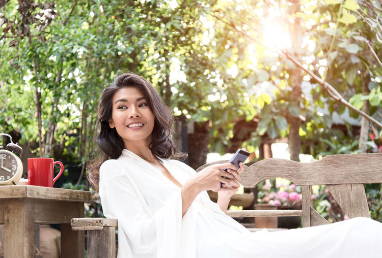Portrait of smiling young woman using smart phone outdoors