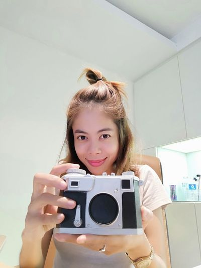 Portrait of smiling mid adult woman holding camera at home
