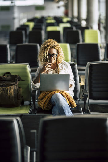 Woman using laptop while sitting at airport