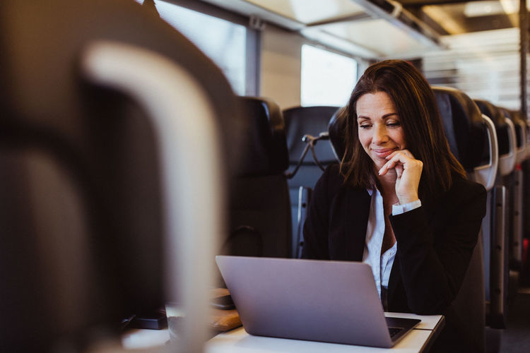 Mid adult woman using mobile phone in office