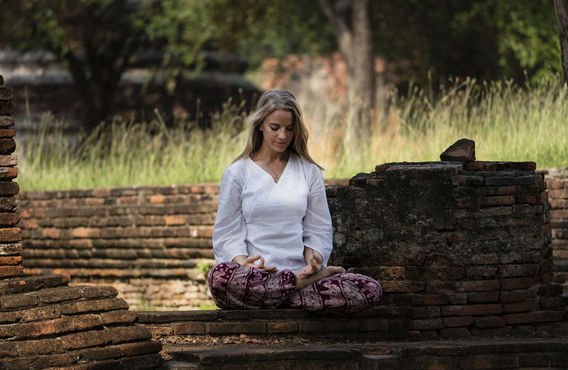 Woman mediating while sitting on brick wall