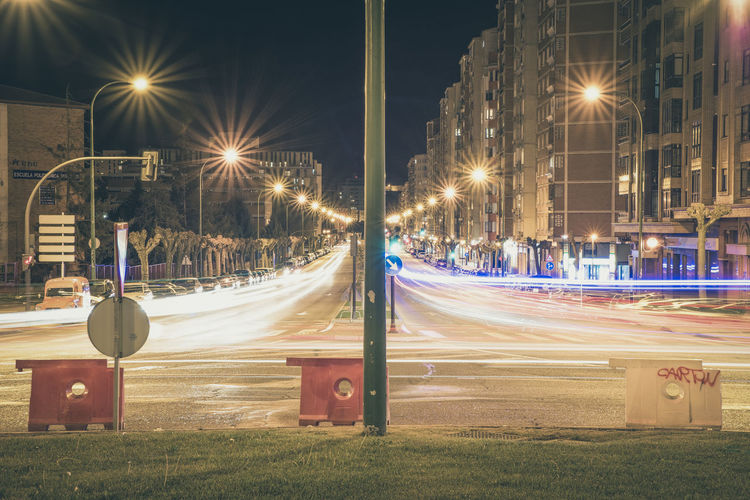 Light Trails On Road Amidst Buildings At Night
