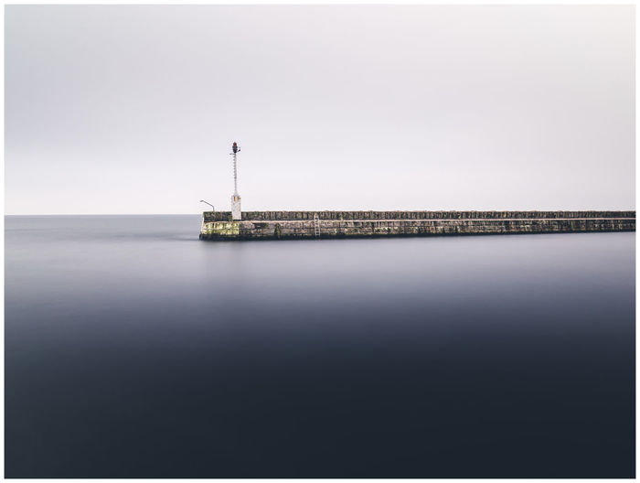 Scenic view of pier at sea against clear sky