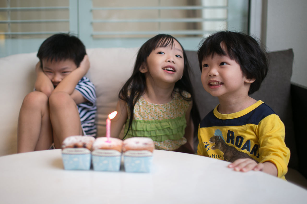 Children sitting by table with illuminated candle on cupcake