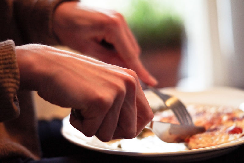 Midsection of person having food in plate with fork and knife on table