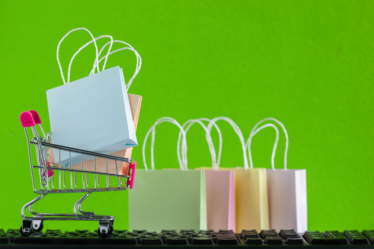 Close-Up Of Figurine Shopping Bags With Shopping Cart On Keyboard Against Green Background