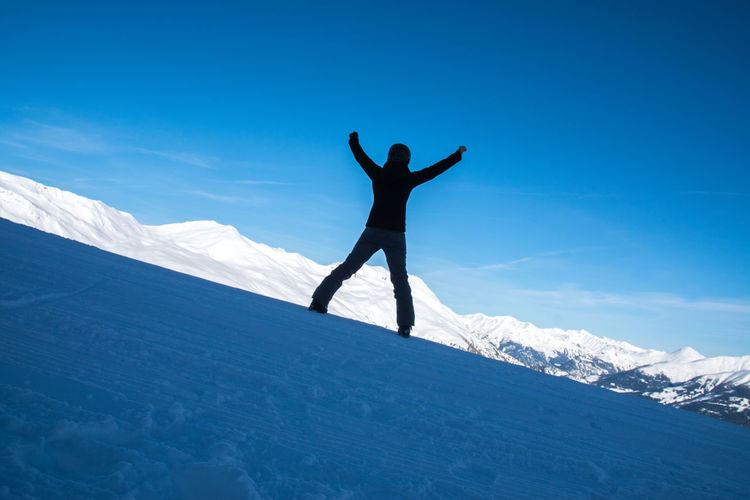 Full Length Of Excited Woman With Arms Raised Standing Against Snowcapped Mountain And Blue Sky