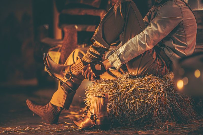 Cowboy in the Barn Wearing Boots While Seating on the Pile of Hay. American Farming Theme. American Cowboy Farmer Leather Texas Beauty In Nature Boot Farming Hay Men Socks Western Wear