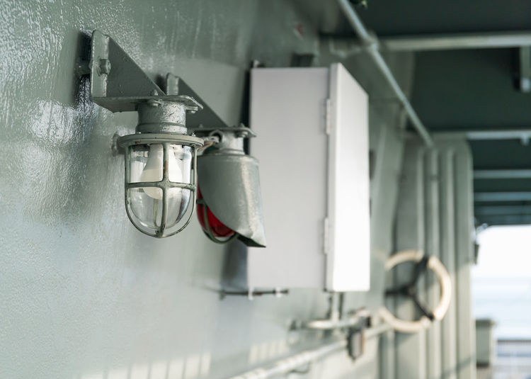 Low angle view of electric lamp hanging on wall