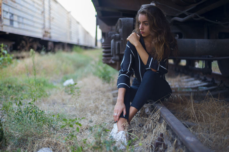 Beautiful Woman Casual Clothing Contemplation Day Field Front View Full Length Hair Hairstyle Land Leisure Activity Lifestyles Looking Nature One Person Outdoors Rail Transportation Real People Sitting Three Quarter Length Track Young Adult Young Women