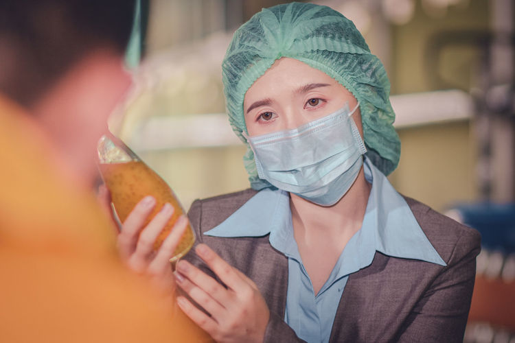 Close-up of woman wearing mask inspecting drink in factory