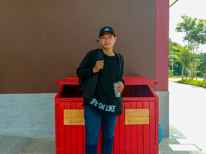 Portrait of young man standing by garbage bin against wall
