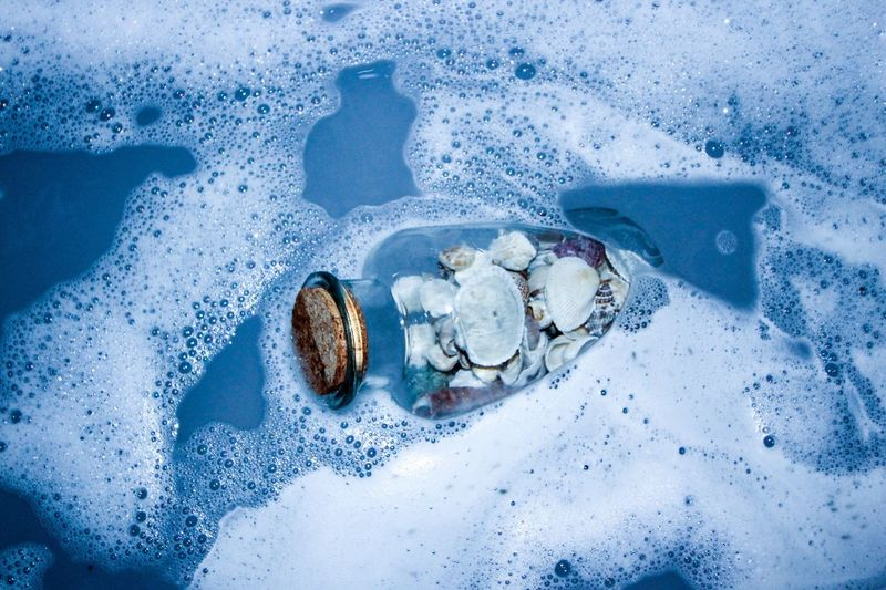 High Angle View Of Seashells In Glass Jar On Shore At Beach