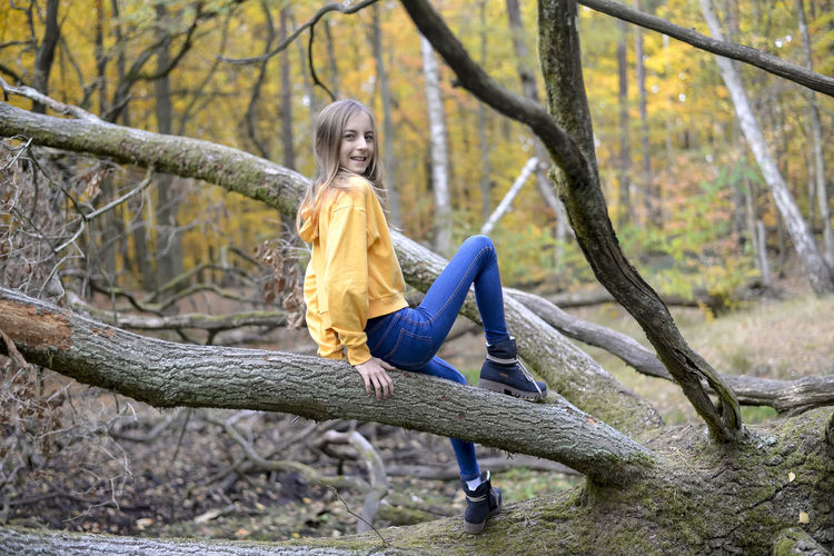 happy teenager Tree One Person Full Length Smiling Casual Clothing Leisure Activity Happiness Nature Trunk Tree Trunk Autumn Childhood Yellow Emotion Lifestyles Real People Child Outdoors Teenager Forest Jeans Laughing