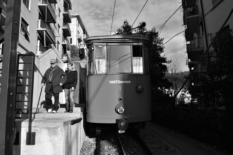 Black And White Bus Cable Car City Life Incidental People Land Vehicle Mode Of Transport On The Move Passenger Train Public Transport Public Transportation Railroad Track Street Train Tramway Transportation