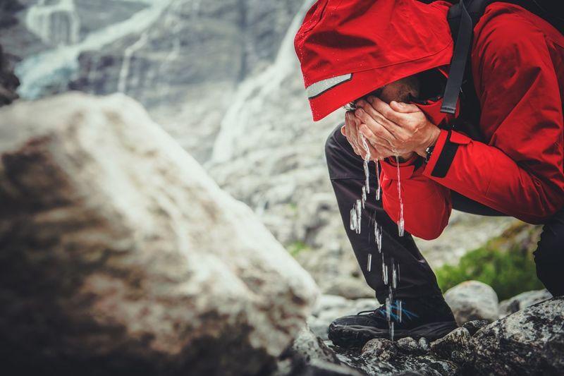 Male hiker drinking water on rocks