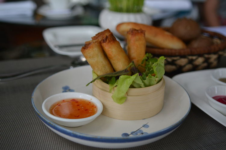 Close-up of spring rolls in bowl at table