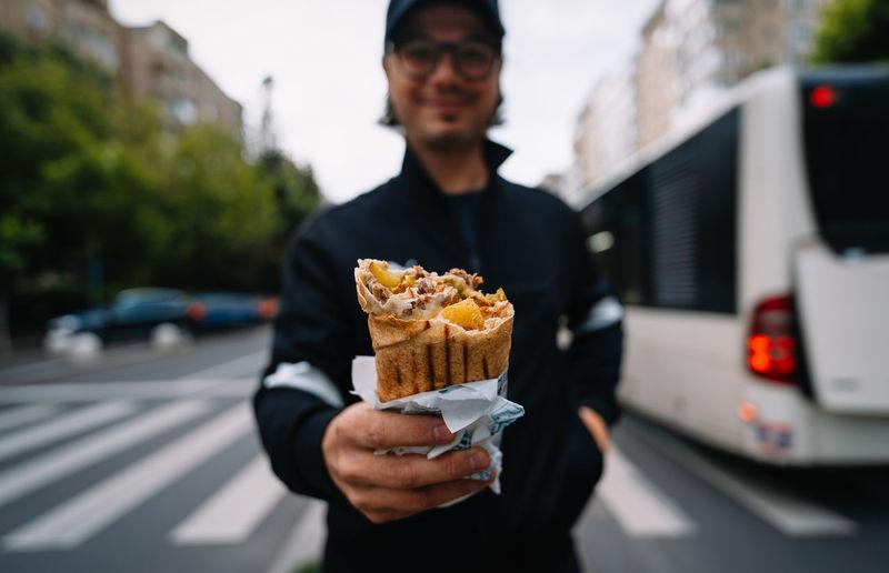 Man holding ice cream standing on street