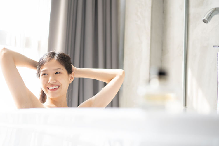 Young Asian woman relaxing in a bath Asian  Asian Girl Woman Girl Japanese  Chinese Korean Smiling Cute Beauty Beautiful Beautiful Woman One Person Indoors  Bath Bathroom Bathtub Bath Time Portrait Happiness Lifestyles Young Women Young Adult Headshot Adult Women Front View Domestic Bathroom Looking At Camera Emotion Human Arm Arms Raised