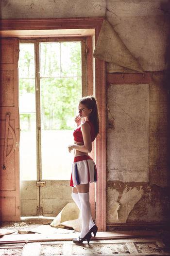 Contemplating female cheerleader standing by door