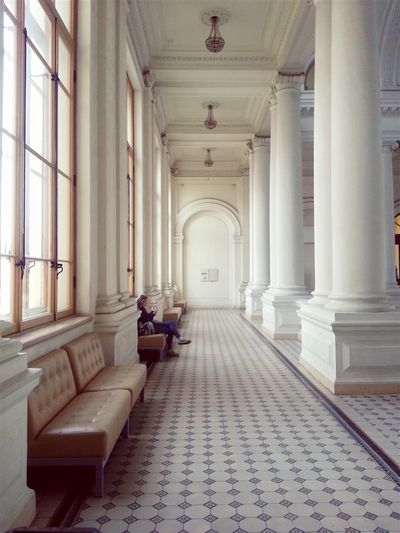 Woman Sitting In Corridor Of Historical Building