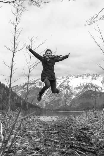 Full length of woman jumping on land against sky
