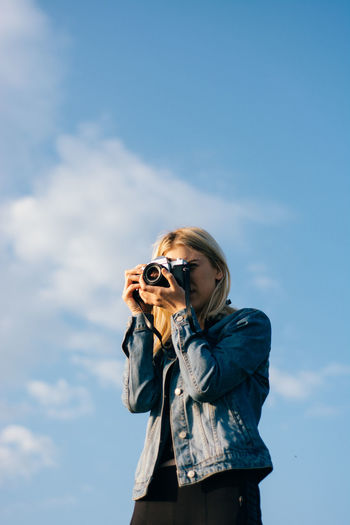 Low angle view of woman photographing with camera against sky