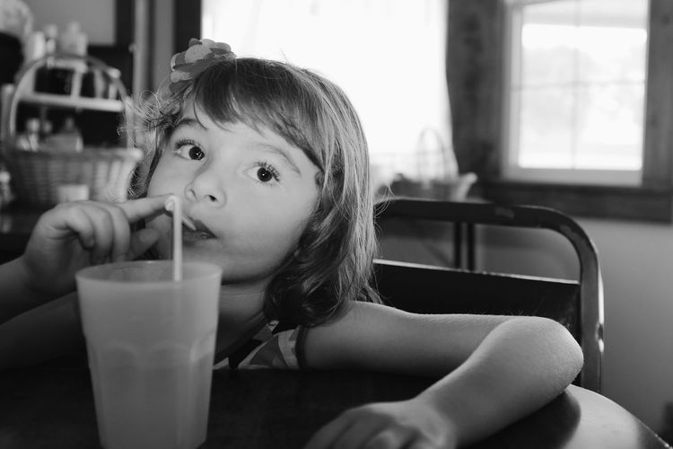Girl looking away while having drink at table