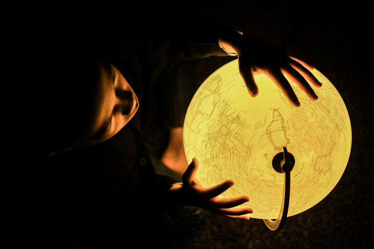 Man holding illuminated lamp in darkroom
