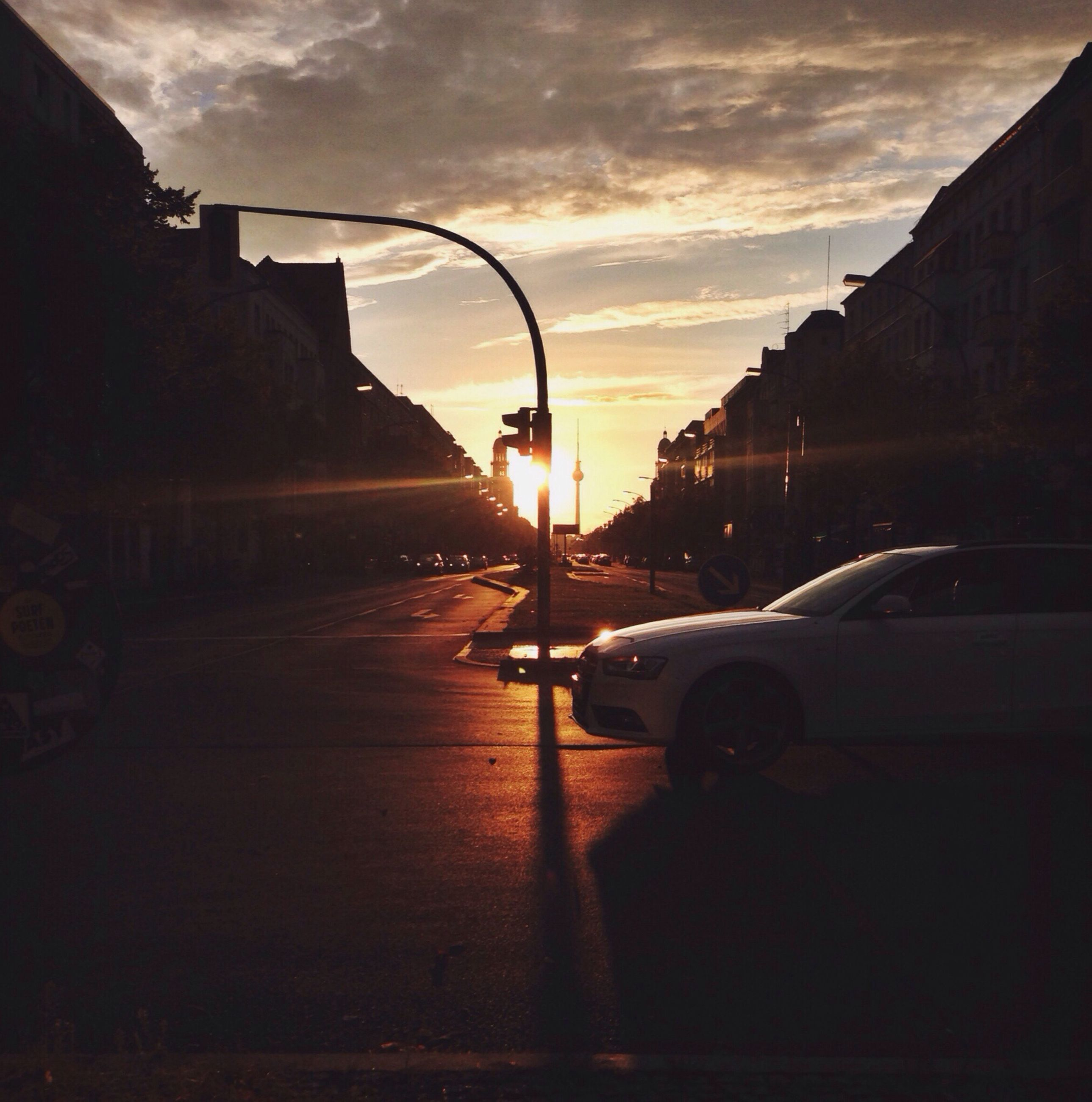 sky, transportation, sunset, mode of transport, building exterior, cloud - sky, built structure, architecture, land vehicle, car, street light, street, silhouette, cloud, sun, sunlight, cloudy, city, nautical vessel, dusk