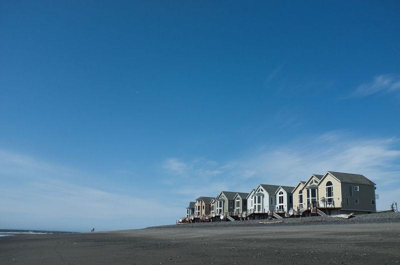 Building on beach against blue sky