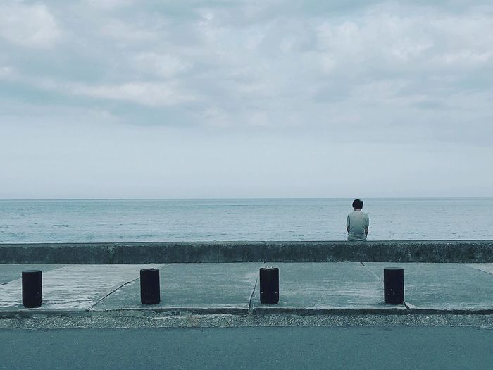 Rear view of man sitting on retaining wall at promenade against cloudy sky