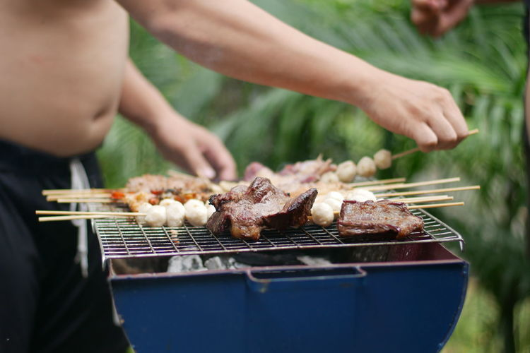 Midsection Of Shirtless Man Preparing Food On Barbecue Grill