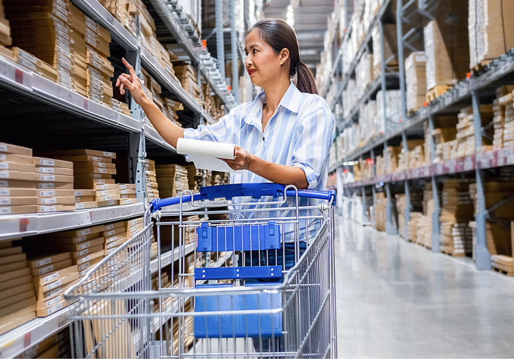 Woman checking list while standing in warehouse