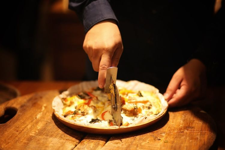 Midsection of man cutting pizza on table