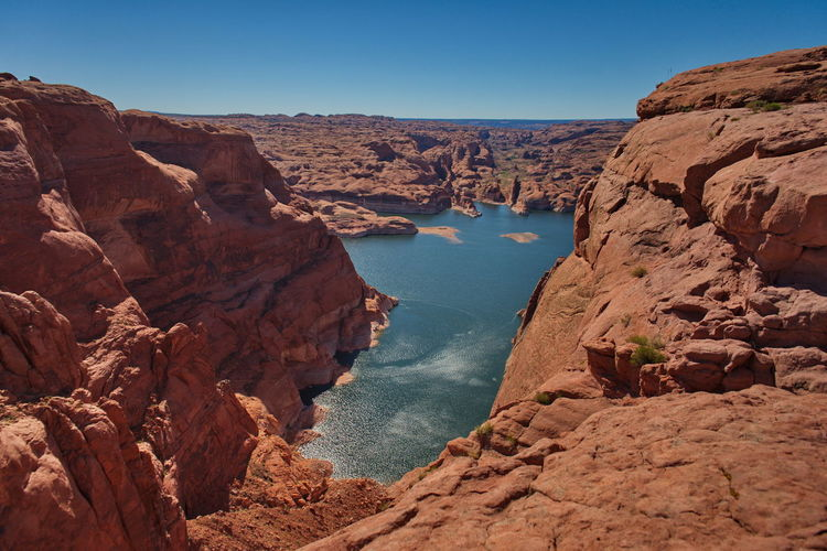 Scenic view of rocks and mountains against clear sky lake powell